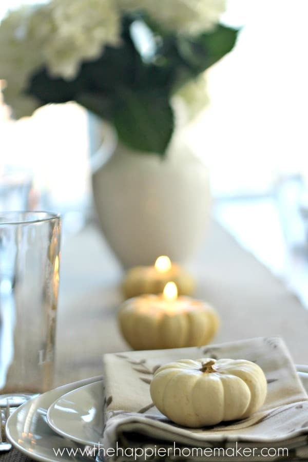 A close up of pumpkins hold tea candles for Thanksgiving dinner