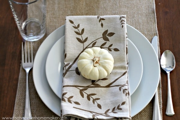 A white plate setting with Autumn napkin with a small white pumpkin on it