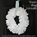 A white DIY trash bag wreath hanging on a dark door