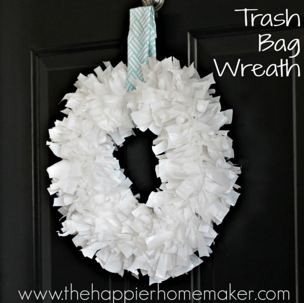 A white DIY trash bag wreath hanging on a dark door