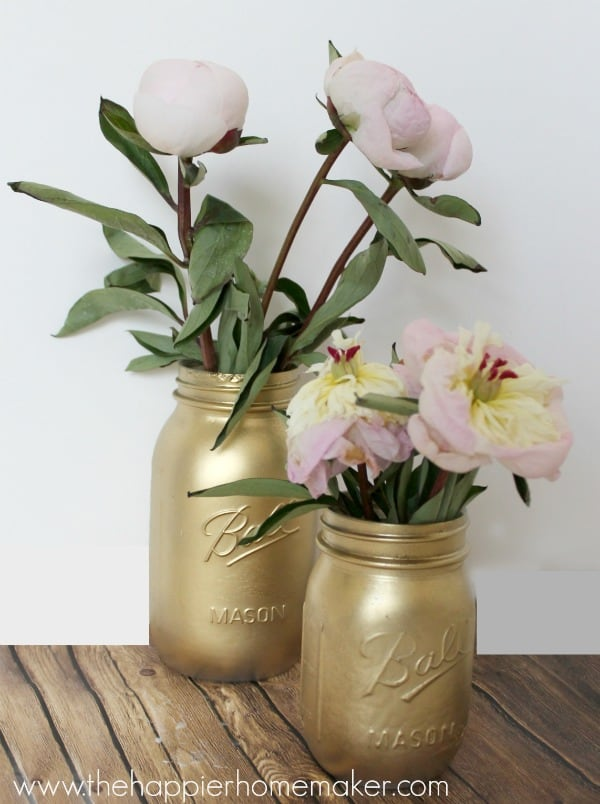 Two gold mason jars serving as vases for pink and white flowers