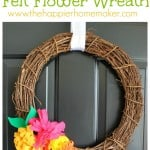 A grapevine wreath hanging on a door with colorful felt flowers on it