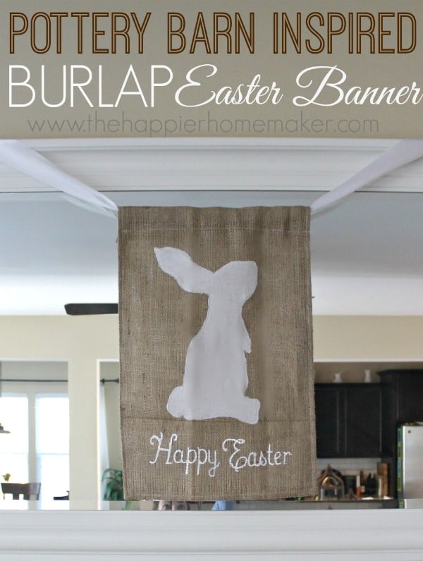"A white cut out of an Easter bunny on a burlap banner with the words ""Happy Easter"" underneath of it"