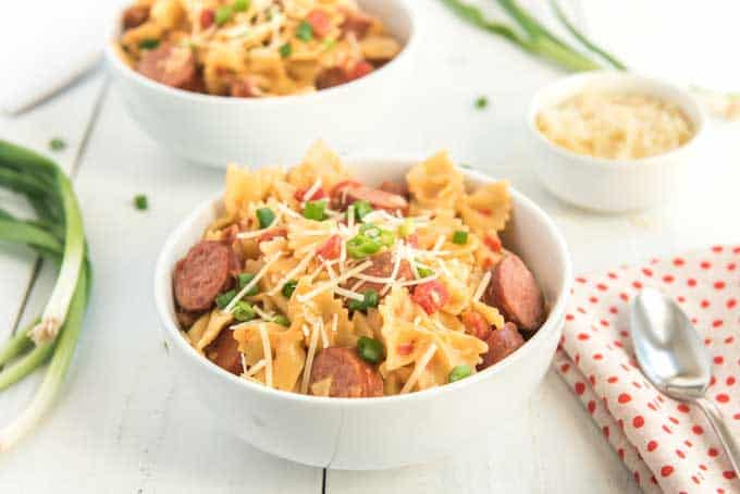 spicy tomato pepper sausage pasta in white bowls on white wood counter