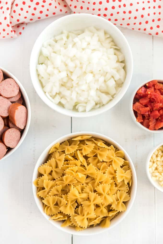 overhead view of spicy sausage pasta ingredients like farfalle pasta, sliced sausage, diced onion, garlic, and tomatoes in white bowls