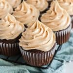 chocolate cupcakes with peanut butter buttercream frosting on blue napkin