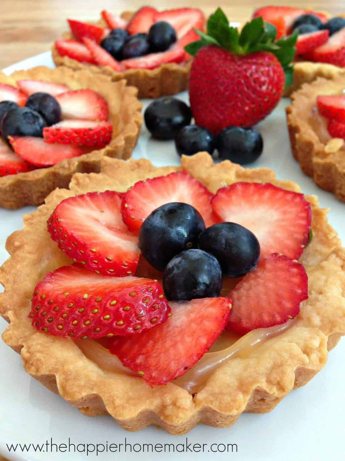 A close up of berry tarts topped with sliced strawberries and blueberries