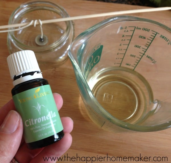 hand holding bottle of citronella oil above measuring cup and mason jar