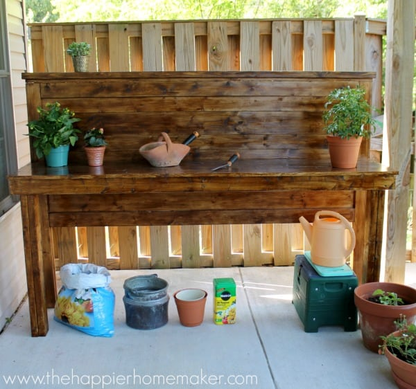 An upcycled headboard made into a potting bench