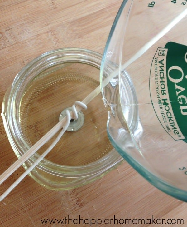 glass measuring cup pouring melted wax into mason jar