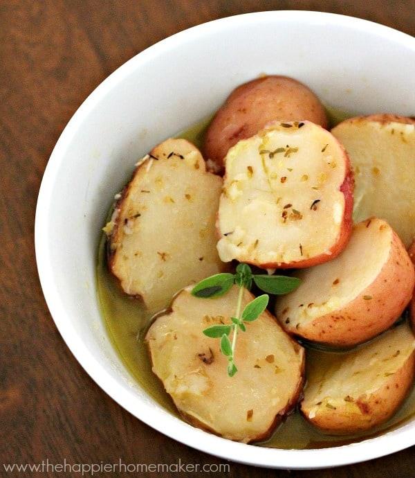 A white bowl full of roasted lemon greek potatoes