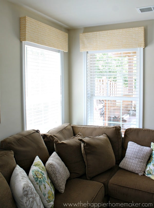 A green sofa with lots of throw pillows in front of corner windows showing DIY valances