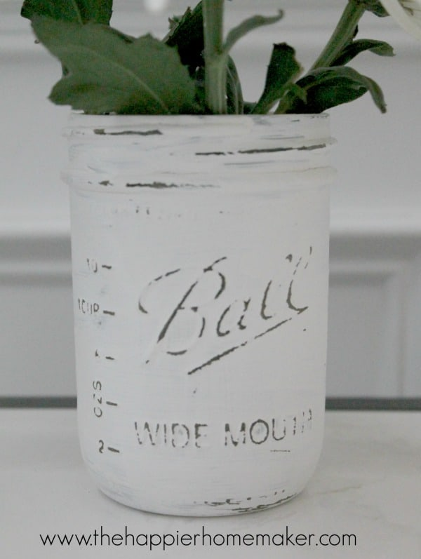 A distressed painted Mason jar used as a planter