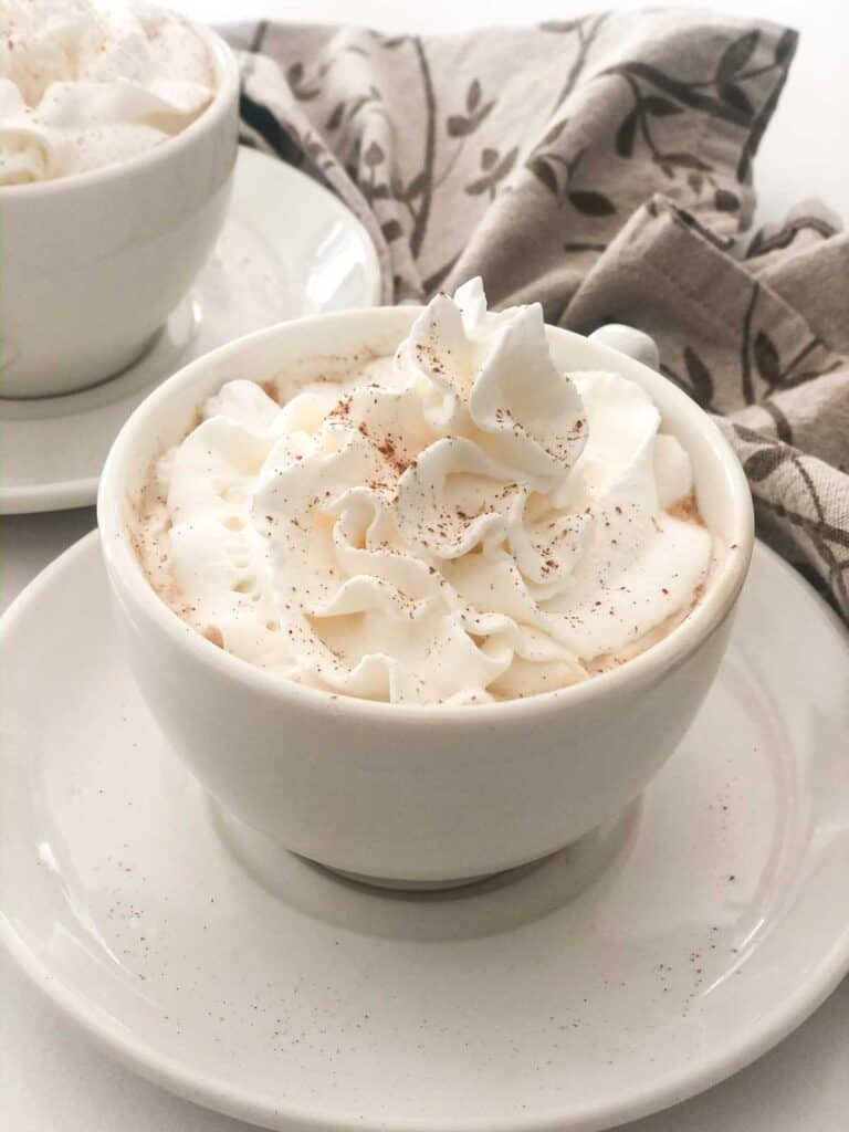 pumpkin spice latte with whipped cream in white mug on saucer
