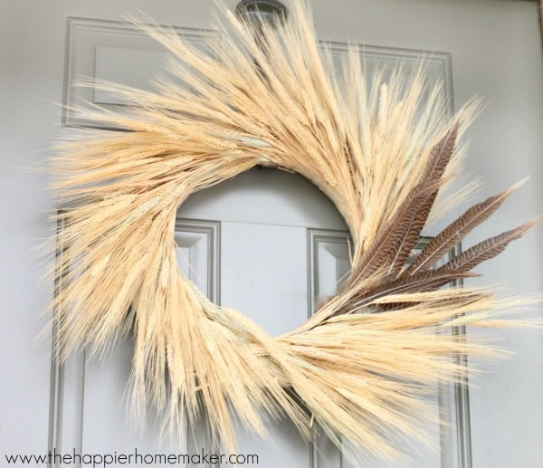A close up of a wheat autumn door wreath with feathers
