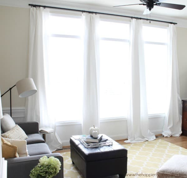 large living room window with white curtains and yellow rug