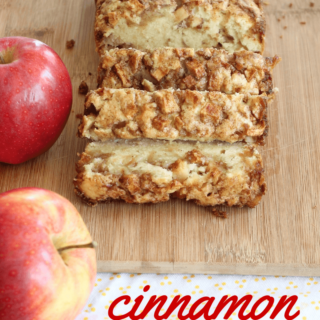 Cinnamon apple bread sliced on a cutting board next to two apples