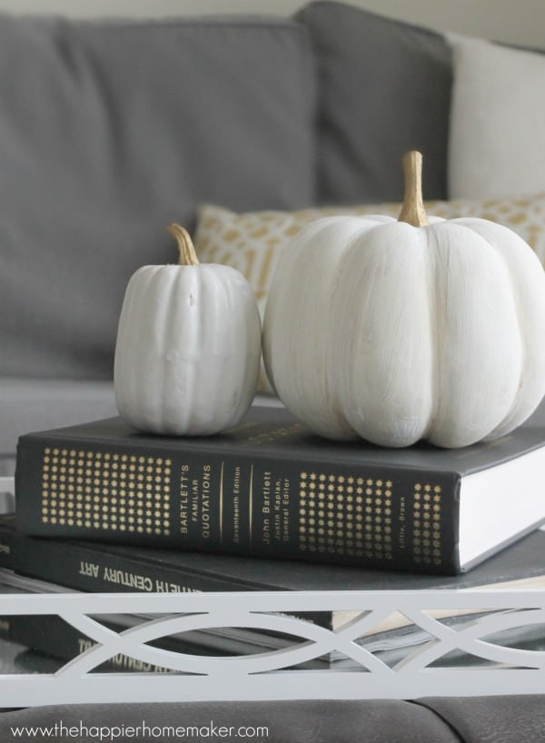 Two fake white pumpkins sitting on a book