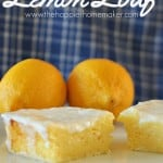 A close up of lemon loaf in front of lemons and a blue and white checkered cloth