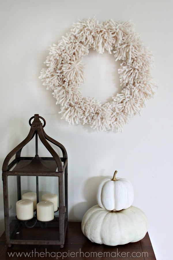 A DIY giant pompom wreath hanging over a white pumpkin and lantern