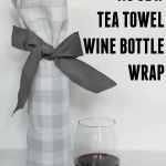 A glass of red wine next to a gray and white checkered DIY wine bottle wrap