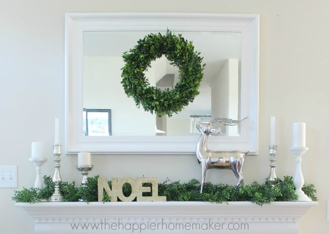 A close up of a mirror with a box tree wreath centered and silver accents with the word NOEL on the mantle