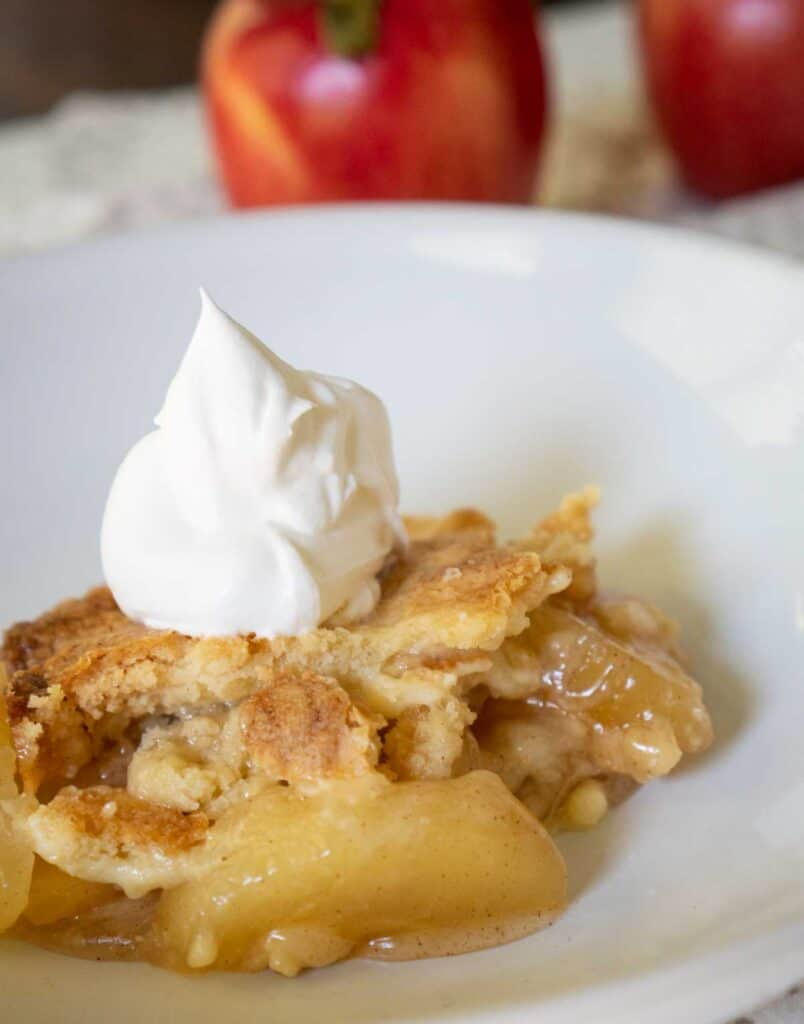 apple dump cake on white plate with whipped cream on top