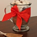 A glass jar full of hot coco mix and mini marshmallows tied with a red ribbon