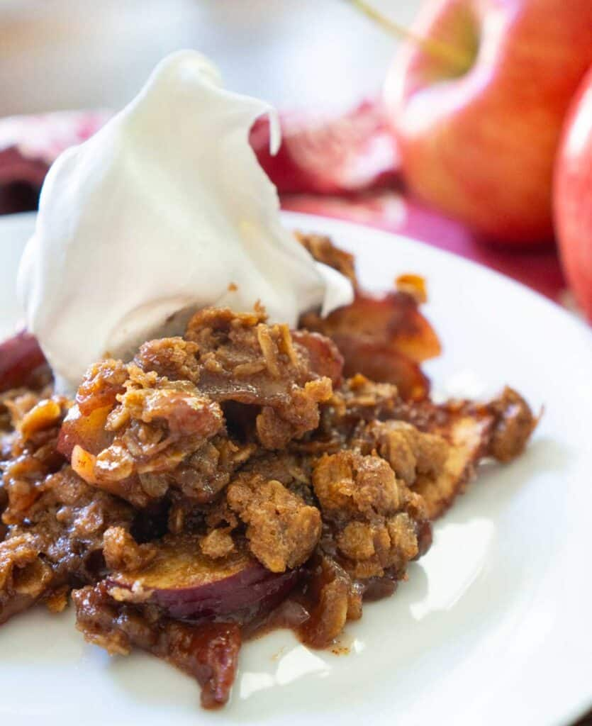 peanut butter apple crisp on white plate with whipped cream on top