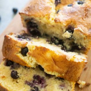 A close up of slices of blueberry cream cheese bread on wood cutting board