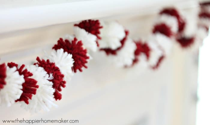 A close up of Valentine's Day mini pom pom garland hanging on a white mantel