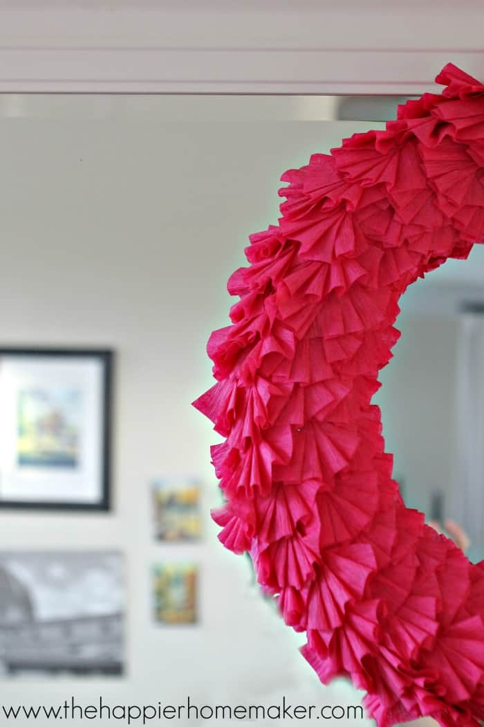 A close up of half of a dark pink Valentine's Day crepe paper ruffle wreath