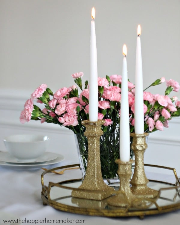 Three no shed glitter candlesticks in front of flowers on a white table