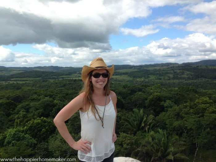 A person standing in front of a tropical forrest with small rolling hills in background.