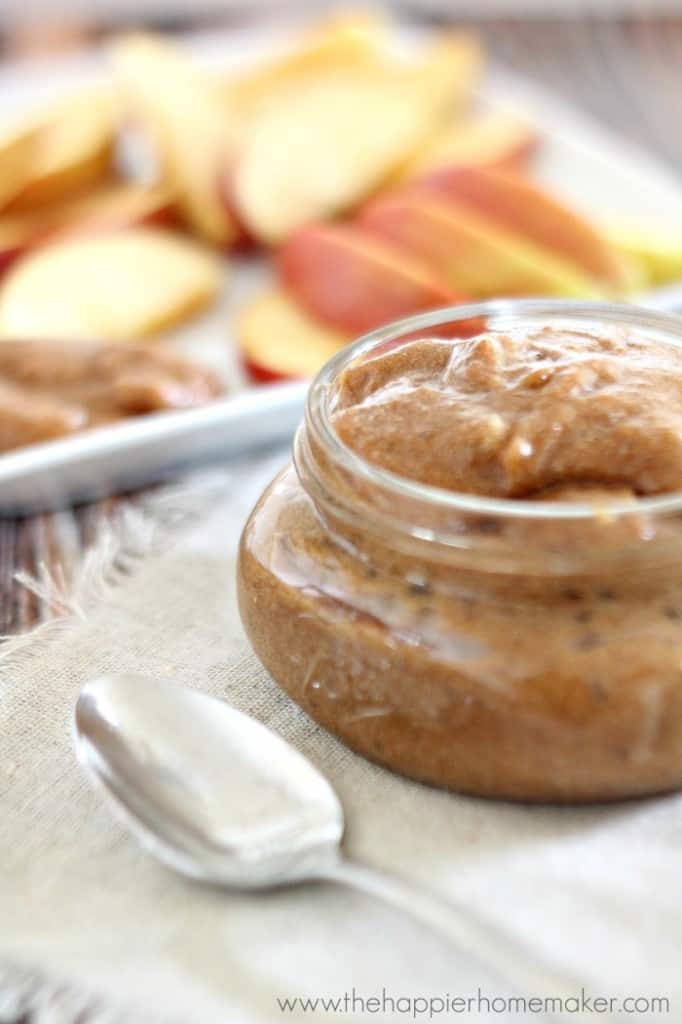 A close up of a jar of easy cookie butter and a silver spoon and apple slices in the background