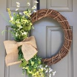A grapevine wreath with green and white flowers tied with a brown bow on an exterior door