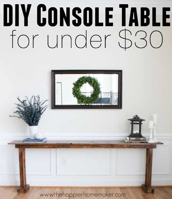 A DIY console table with greenery, lantern and candlesticks on it