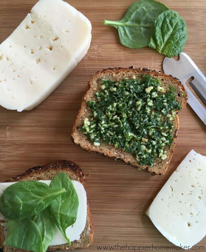 An in-process picture of pesto on slice of bread with cheese and spinach near it
