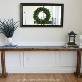 A DIY console table with greenery and a lantern on it