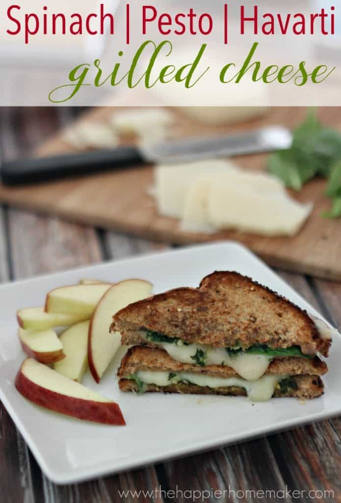 A close up of spinach pesto havarti grilled cheese cut in half with apple slices