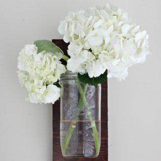 Two hydrangea flowers in a DIY mason jar wall vase