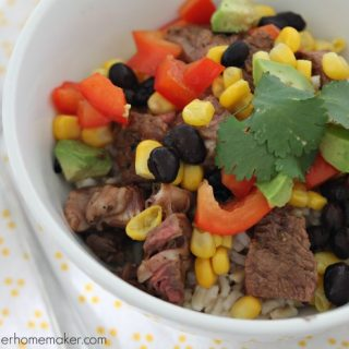 A close up of a bowl of a burrito bowl topped with cilantro, corn and red peppers