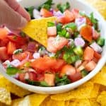 hand holding totrtilla chip with pico de gallo in white bowl in background