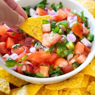 hand holding totrtilla chip with pico de gallo in white bowl in background
