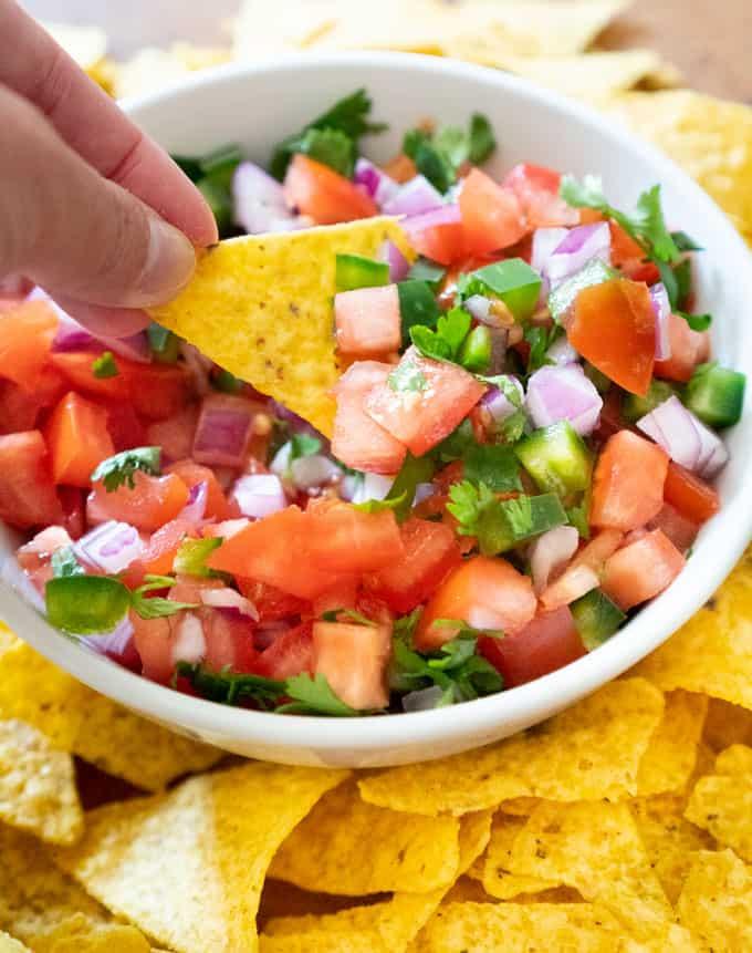 homemade pico de gallo in a white bowl with tortilla chips