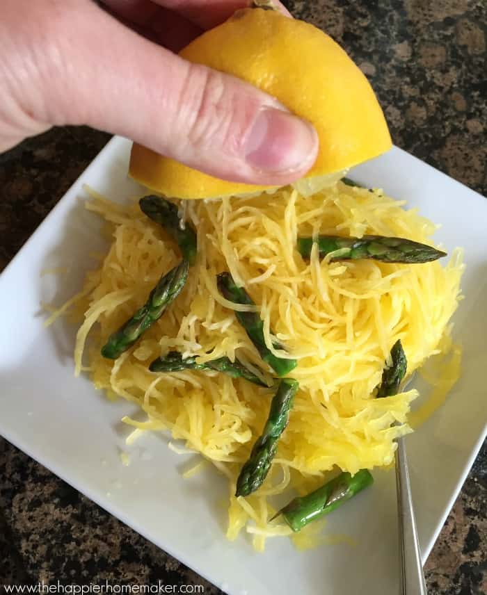 Someone squeezing half of a lemon on top of spaghetti squash and asparagus