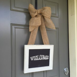A grey exterior door with a welcome sign hung by brown ribbon
