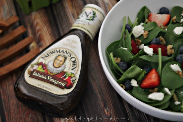 An above picture of a summer berry walnut balsamic salad next to Newman\'s Own salad dressing