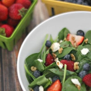 A summer berry walnut balsamic salad next to strawberries and blueberries