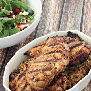 A white serving dish full of grilled chicken next to a salad